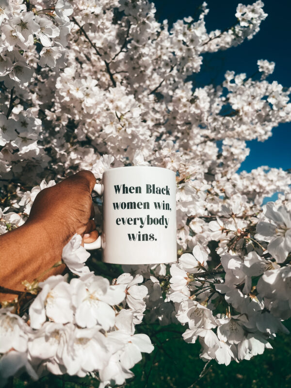 When Black Women Win Everybody Wins mug being held by the handle in a cherry blossom tree